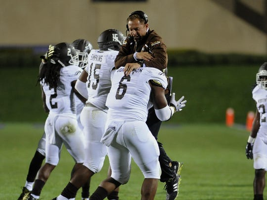 Western Michigan head coach P.J. Fleck leaps on Roosevelt Donaldson (6) during a 2013 game against Northwestern.