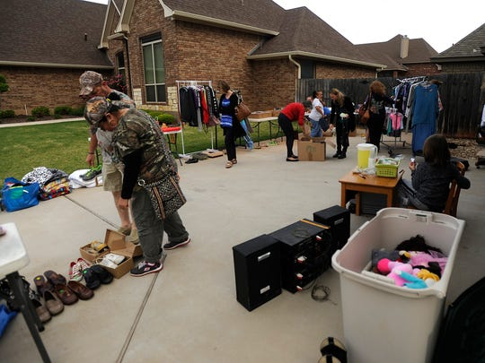 Garage sale goers pick through items for sale at a multi-family garage sale on Saturday, April 1, 2017, in south Abilene.