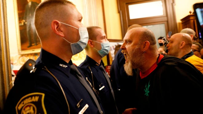 Michigan State Police bar protesters from entering the chambers of the Michigan House of Representatives on April 30 during a rally for the reopening of businesses on the steps of the Michigan State Capitol in Lansing.
