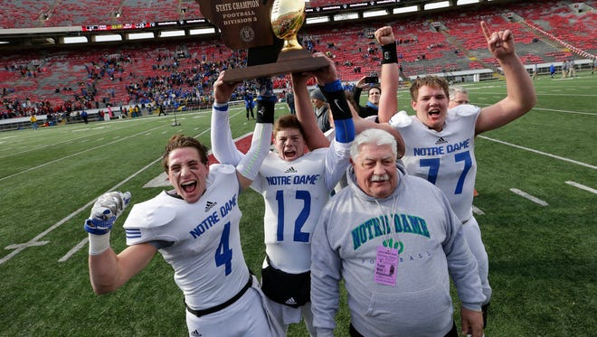 Green Bay Notre Dame senior football players Vinny Pallini (4), Robert Petitjean (12) and Blake Olejniczak (77) celebrate their WIAA Division 3 state championship victory with coach John Nowak on Nov. 20 at Camp Randall Stadium in Madison. Notre Dame's championship run is Press-Gazette Media's top prep sports story of 2015.