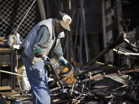 Paul Jaramillo Sr., 94, goes through the remains of his tool shed. A fire scorched the shed and the tools inside.