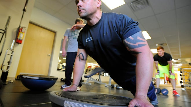 Lansing Police Officer Aaron Terrill watches his form as he works out with others at the Iron Brotherhood Program at the DeWitt YMCA Wednesday. The program is designed to improve well-being and quality of life for men who have served in fields that have caused emotional trauma like police, military veterans, EMTs, firefighters and others.