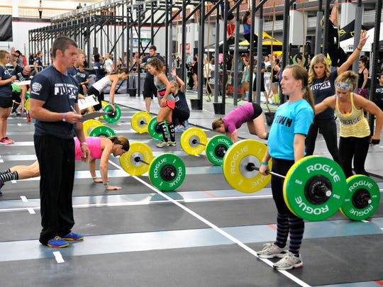 Athletes deadlift weights, do burpees and then climb a rope during a timed event Friday at the Granite Games in Halenbeck Hall Fieldhouse.