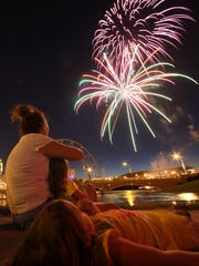 D'anne Dzon and her daughters Samantha, 4, and Taylor, 4, of Des Moines watch the fireworks during Yankee Doodle Pops in 2010.