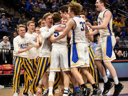 St. Cloud Cathedral players celebrate their win over Esko in triple overtime Wednesday, March 21, in the first round of the state Class 2A boys basketball tournament at Target Center in Minneapolis.