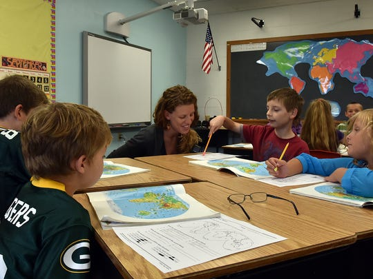 Hannah Nerenhausen, an emergency permit teacher, aids third-grade student Nicholas Mohn in learning the continents at Washington Island School on Sept. 11.