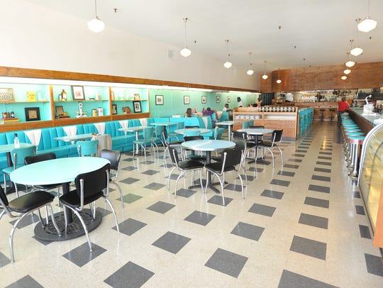 The turquoise barstools and booths are iconic pieces