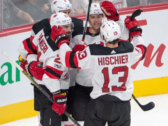 New Jersey Devils center Nico Hischier (13) celebrates with teammates Kyle Palmieri (21), Dalton Prout (5) and Taylor Hall (9) after scoring during first period an NHL preseason hockey game against the Montreal Canadiens, Thursday, Sept. 21, 2017, in Montreal. (Ryan Remiorz/The Canadian Press via AP)