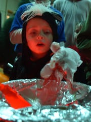 Costumed as a skunk, Grant Cotter of Sheboygan feels for gooey stuff in a large bowl covered with foil during the last year's Halloween party hosted by the Baileys Harbor Community Association. Participants tried to guess the substances or objects hidden under the foil.