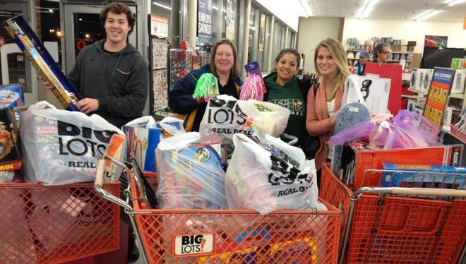 Corlie Budd, far left, shops with fellow Greene Turtle employees for gifts with money earned during the company's annual Tips for Tots initiative.