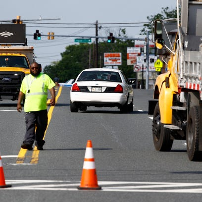 An emergency vehicle passes a roadblock near a scene