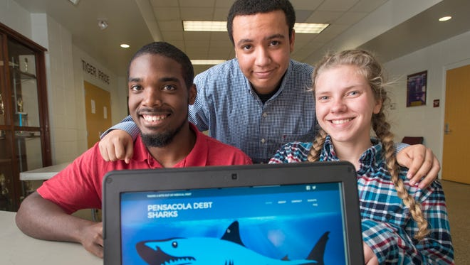 High school juniors Josh Williams, left, to right, Samir Boussarhane, and Falen McClellan created the Pensacola Debt Sharks for their International Baccalaureate community development project at Pensacola High School.  The goal of the Debt Sharks is to raise money to help relieve one million dollars of medical debt for people in the Pensacola and Mobile area.