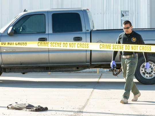 A photographer with Doña Ana Sheriff's Office investigates after an industrial accident occurred at Overkill Racing and Chassis, killing one person on Saturday, December 10, 2016.