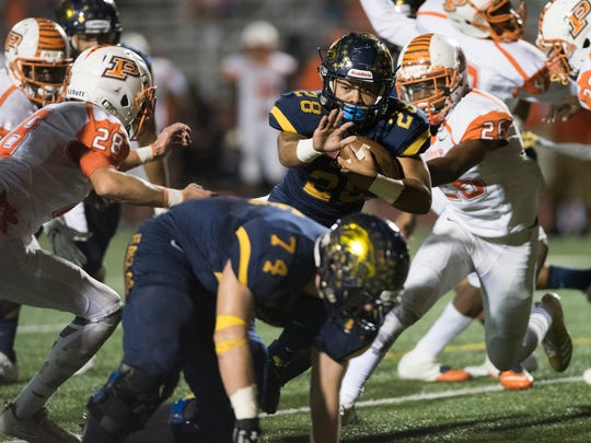 Elan Sommala of Naples breaks through a hole to score a touchdown in the game against Sunrise-Piper at Naples High Friday night, November 3, 2017.