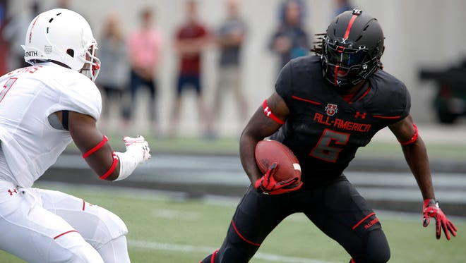 Team Armour running back Kareem Walker (6) eludes Team Highlight outside line backer Ben Davis during the first half of the 2016 Under Armour All-American Game at Orlando Citrus Bowl Saturday.