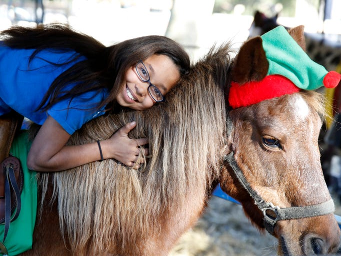Risa Carroll, 11, rides her pony Cookie Dough at the