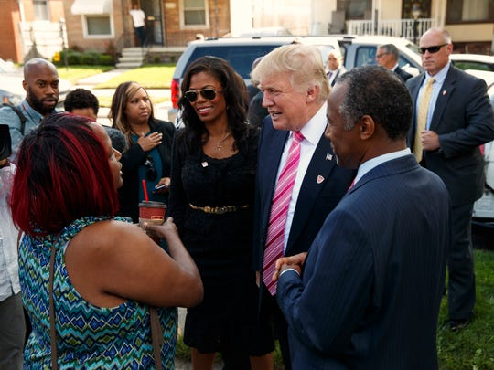 Felicia Reese, left, talks with Republican presidential candidate Donald Trump and Dr. Ben Carson, during a tour of Carson's childhood home, Saturday, Sept. 3, 2016, in Detroit. Reese has lived in Carson's boyhood home since 1992.