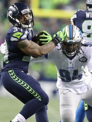 Lions defensive end Ezekiel Ansah misses a tackle on Seahawks running back Thomas Rawls during the second quarter the playoff game on Saturday in Seattle.