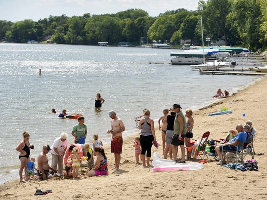 Families enjoy the beach at Schroeder Regional Park & Campground on Cedar Lake near Annandale. Weight determines how sand and other objects are shaped by water.
