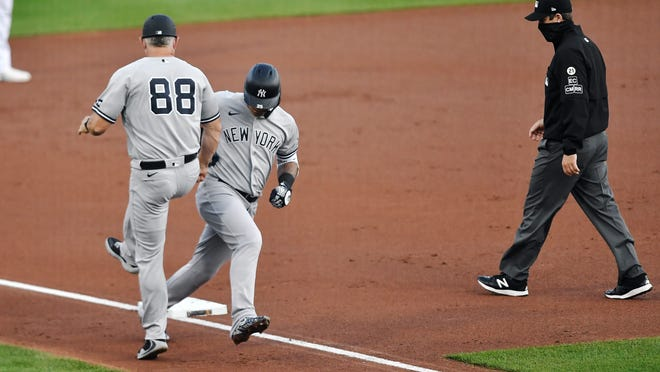 New York Yankees' Gleyber Torres celebrates with third base coach Phil Nevin (88) after hitting a solo home run against the Toronto Blue Jays during the second inning of a baseball game in Buffalo, N.Y., Wednesday, Sept. 9, 2020.