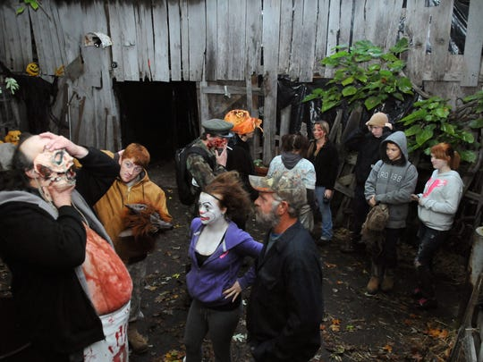 A group relaxes in the courtyard before opening Friday at the Haunted Farm in Pleasantville.