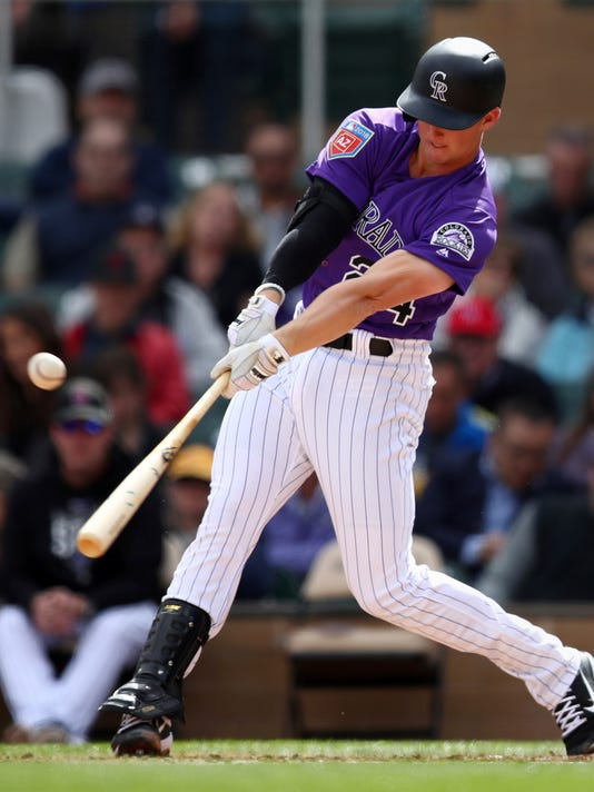 Colorado Rockies' Ryan McMahon connects for an RBI-double during the second inning of a spring training exhibition baseball game against the Arizona Diamondbacks on Friday, Feb. 23, 2018, in Scottsdale, Ariz. (AP Photo/Ben Margot)