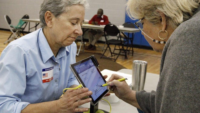 Voter Janice Christian, right, signs in with poll worker Valerie Fronczak in the Woodward Park Community Center on Election Day in 2017. Ohio's county boards of elections still need to recruit nearly 12,000 Democrats and almost 15,000 Republicans to be poll workers to hit the state's goal of being prepared for cancellations.