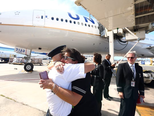 Captain Greg Everhard hugs Flight Attendant Jennifer