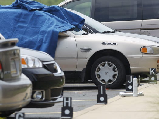A blanket is draped over a car after a shooting in the parking lot of Jordan Manufacturing in Monticello left three people dead Tuesday, Aug. 5, 2014.