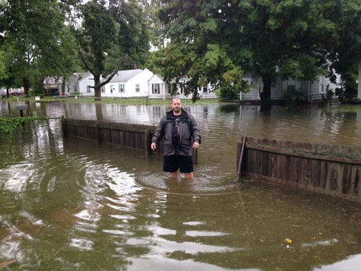 A man wades through flood water on the 2300 block of South Vine Street in Muncie, Friday, Aug. 22, 2014.
