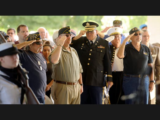 Veterans stand and salute as the Colors are posted by Flying Eagles Squad, United States Naval Sea Cadet Corps, Monday during the Memorial Day Services at the Visalia Public Cemetery. The services were presented by the Avenue of the Flags Veterans Association.