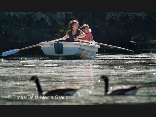 Karen Herrera, 15, left, of Tulare paddles her sister Axel Herrera, 9, around the pond in Mooney Grove Park in  2012.