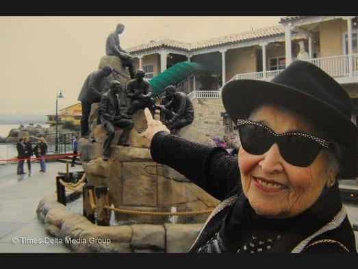 Laura Davidian of Visalia points to the Cannery Row Monument at Steinbeck Plaza at Cannery Row in Monterey which features her late husband Harry Davidian, a Tulare County farmer turned developer. He and the late car dealer George Zarounian paired up with Ted Balestreri and Bert Cutino to buy up property at the deteriorating cannery row in Monterey and developed it into a waterfront tourist attraction.