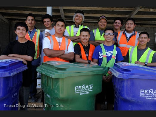 Eleven members of the Young Men's Initiative take a moment to pose for a picture at Pena Disposal in Dinuba on Aug. 1, 2014. They helped distribute 10,000 new recycling cans to residents and picked up the now obsolete divided cans as a service project.