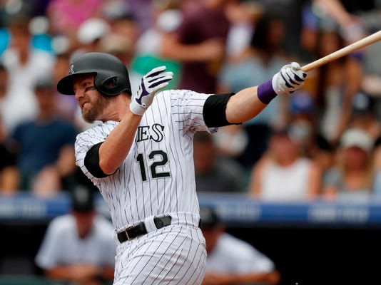 FILE - In this July 23, 2017, file photo, Colorado Rockies' Mark Reynolds bats during the team's baseball game against the Pittsburgh Pirates in Denver. A person familiar with the negotiations says Reynold--a free agent--and the Washington Nationals have agreed to a minor league contract and the first baseman would get a $1.5 million, one-year deal if added to the 40-man roster. The person spoke to The Associated Press on condition of anonymity Friday, April 13, because the agreement is subject to a successful physical. (AP Photo/David Zalubowski, File)