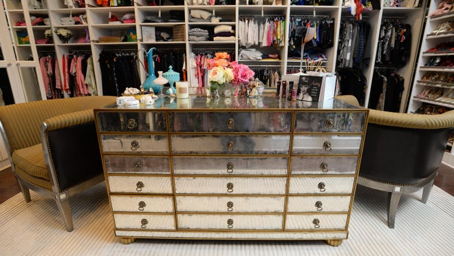 Offering plenty of counter space, shelving and seating a luxury closet Shreveport resident Melanie Johnson created for a client features an island of an aged eglomise mirrored chest with antique gold leaf accents.