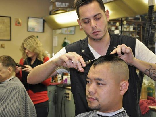Barber Chris Benetatos gives a haircut to former Army