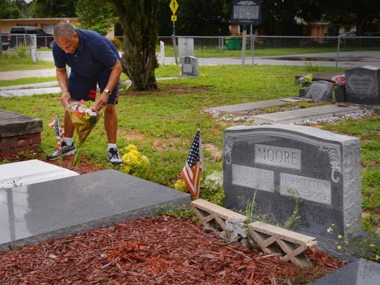 """Drapher """"Skip"""" Pagan, son of the late Juanita Evangeline Moore, daughter of slain civil rights leaders Harry T. and Harriette V. Moore, putting flowers on his mothers' grave in Mims.  He is honored that some of his grandparent's possessions will be displayed at the Smithsonian National Museum of African American History & Culture."""