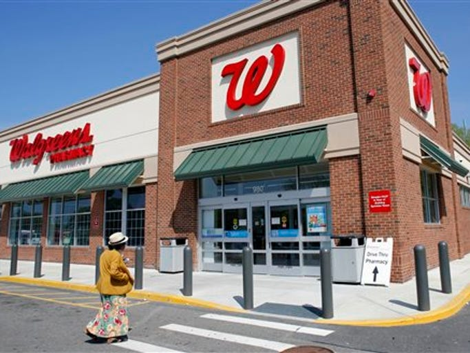 In this Wednesday, May 14, 2014 photo, a customer walks toward an entrance to a Walgreens store, in Boston. Walgreen plans to keep its roots firmly planted in the United States, saying Wednesday, Aug. 6, 2014 it will no longer pursue an overseas reorganization that would have trimmed the amount of U.S. taxes it pays. Walgreen Co. had drawn criticism for considering an inversion, in part because it receives a portion of its revenue through government funded programs that help cover the sick and elderly people.