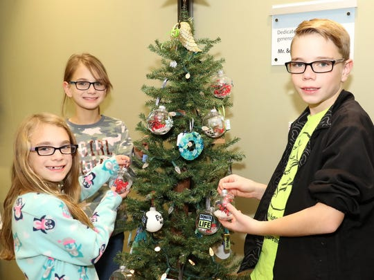 Addison, Kortney and Matthew Witherow decorated a tree with ornaments made during a previous Gift of Life event held by Genesis HealthCare System and Lifeline of Ohio. The event is for families of organ and tissue donors to honor their late loved ones.