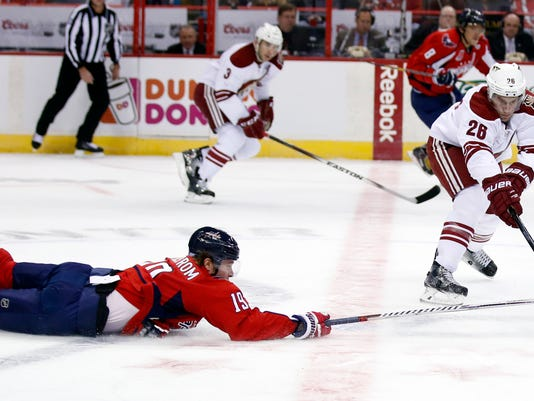 Washington Capitals center Nicklas Backstrom (19), from Sweden, dives for the puck with Arizona Coyotes left wing Lauri Korpikoski (28), from Finland, in the first period of an NHL hockey game, Sunday, Nov. 2, 2014, in Washington. (AP Photo/Alex Brandon)