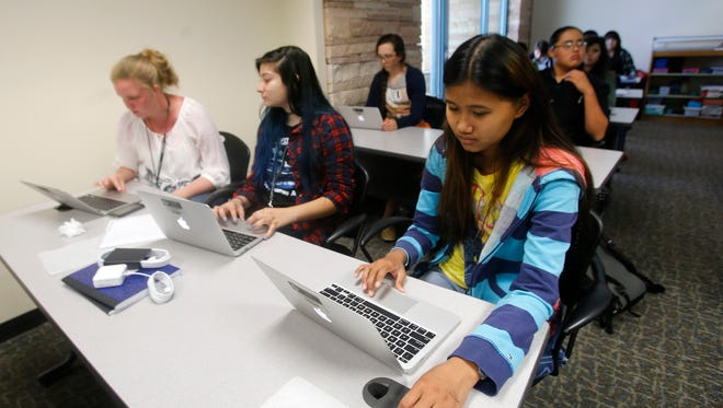 From left, EmmaRaye Gilmore, Daira Trujillo and Sepphora Llanes use their new computers on Monday during math class at San Juan College High School in Farmington.
