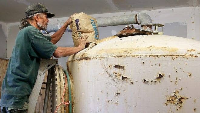 AV Water employee Joe Moya adds pumice to a filtration system on Sept. 27 in the Harvest Gold subdivision, east of Bloomfield.