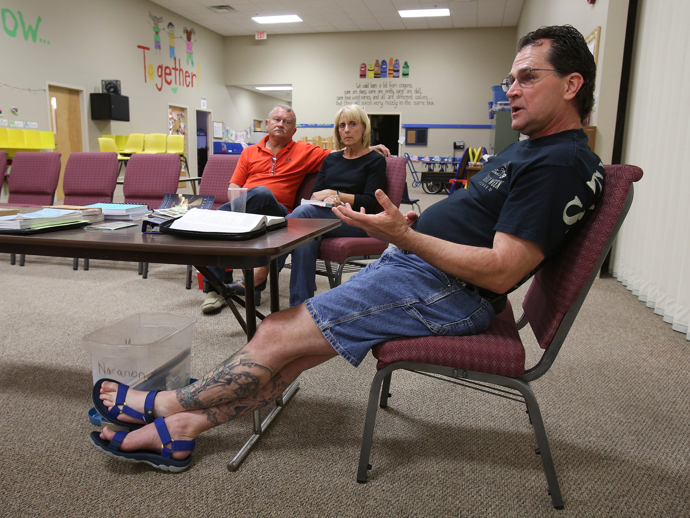 Facilitator Ed Small, right, makes remarks during a