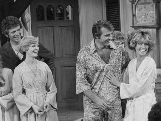 """FILE - In this Jan. 20, 1977 file photo, actress Farrah Fawcett-Majors, right, joins her husband Lee Majors in a television appearance together in the sit-com """"The Brady Bunch."""" At left are actors Geri Reischl, Robert Reed and Florence Henderson. Henderson, the wholesome actress who went from Broadway star to television icon when she became Carol Brady, the ever-cheerful mom residing over """"The Brady Bunch,"""" has died at age 82. She died surrounded by family and friends, her manager, Kayla Pressman, said in a statement late Thursday, Nov. 24, 2016. (AP Photo/George Brich, File)"""