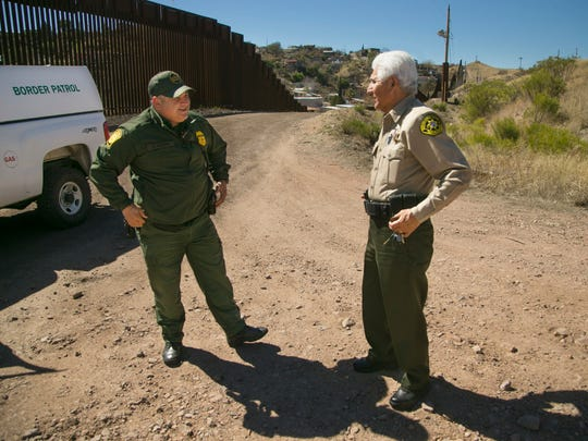 Santa Cruz County Sheriff Tony Estrada, speaks to a U.S. Border Patrol Agent that did not wish to be identified at the border fence that separates the United States from Mexico in Nogales, Ariz.,