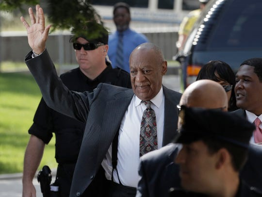 Bill Cosby waves as he arrives at the Montgomery County