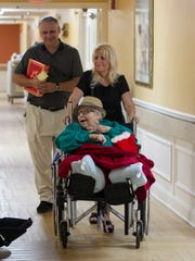 An Bacheler pushes her mother, Florence Muchnick, back to her room during a visit on Christmas Eve. Though Muchnick retired a millionaire, her money has run out because of the high cost of her care. She is now on Medicaid and in the only facility that her daughter could find for her. Self-paying patients recieve priority at the nicer facilities.