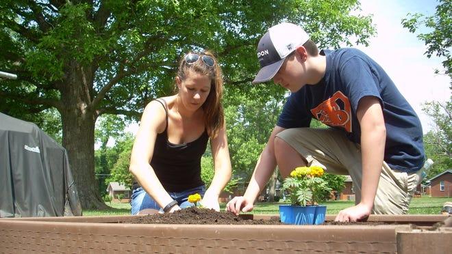 Volunteers Morgan James and Jake Arning set marigold plants in each corner of the garden at Oak Court.
