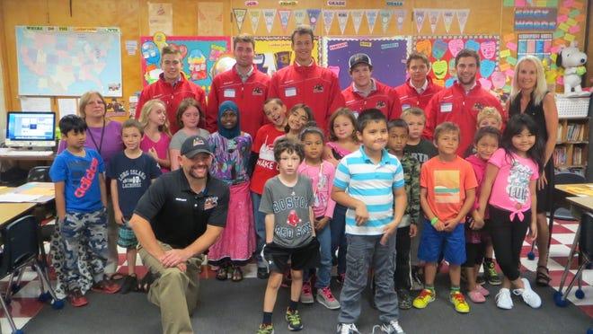Members of the Vermont Lumberjacks hockey team pose with third-graders at John F. Kennedy Elementary School in Winooski.